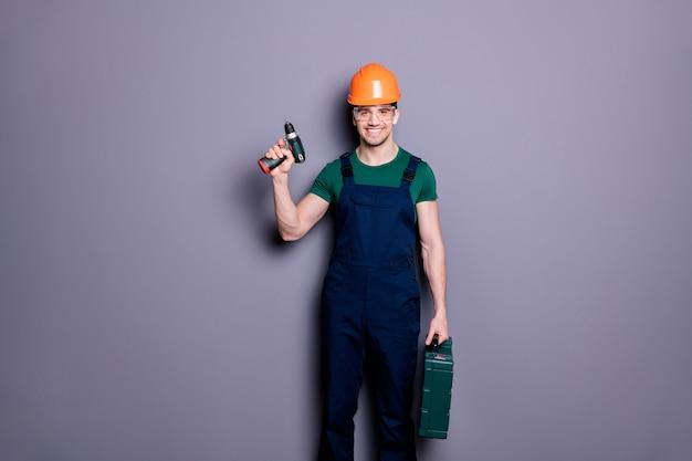 Portret van positieve zelfverzekerde koele reparateur man klusjesman klaar om appartement kamer te reconstrueren houden boor gereedschapskist dragen oranje uniform geïsoleerd over grijze kleur muur