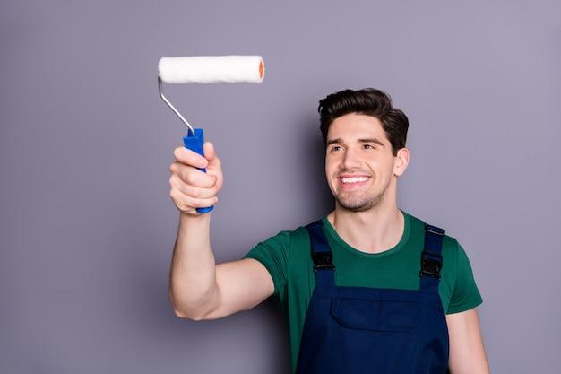 Portret van positieve zelfverzekerde werkman huisschilder verf kamer met witte roller renoveren appartement dragen groene t-shirt blauwe uniforme overall geïsoleerd over grijze kleur muur