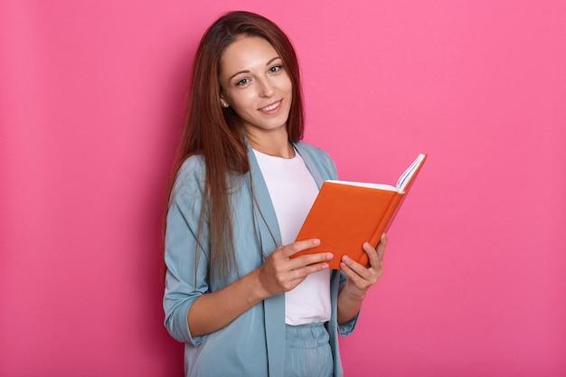 Portret van positieve zoete jonge vrouw met lang haar, gekleed in blauw pak, in een goed humeur