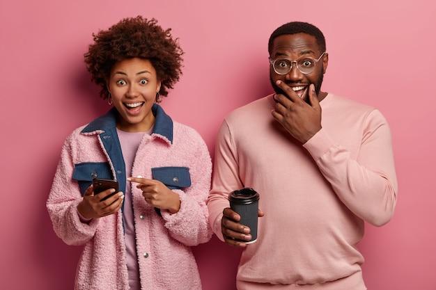 Portret van positieve zwarte afro-amerikaanse vrouw en vriend giechelen gelukkig