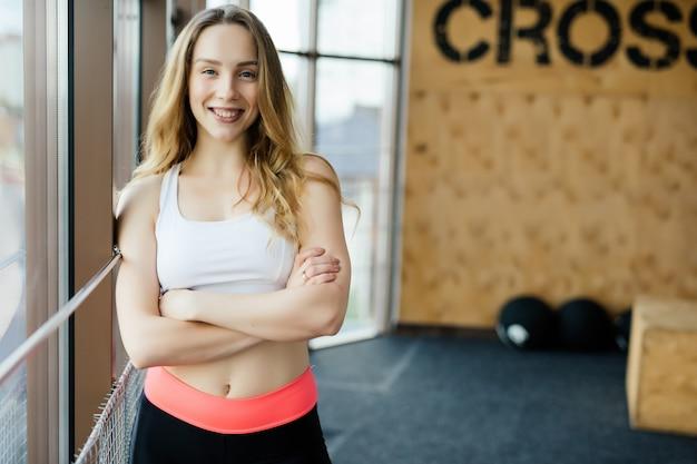 Portret van positiviteit en meisje glimlachend in de camera en poseren met gekruiste armen in de sportschool.