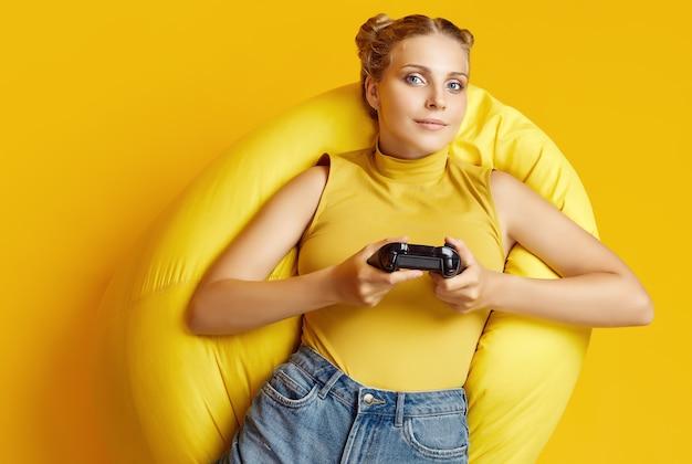 Portret van prachtig gelukkig blonde gamer meisje met joystick liggend in een zakstoel op gele achtergrond