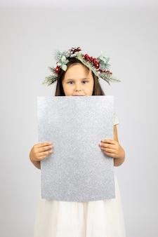 Portret van prachtig meisje in witte jurk en kerstkrans met zilveren glanzende poster geïsoleerd ...