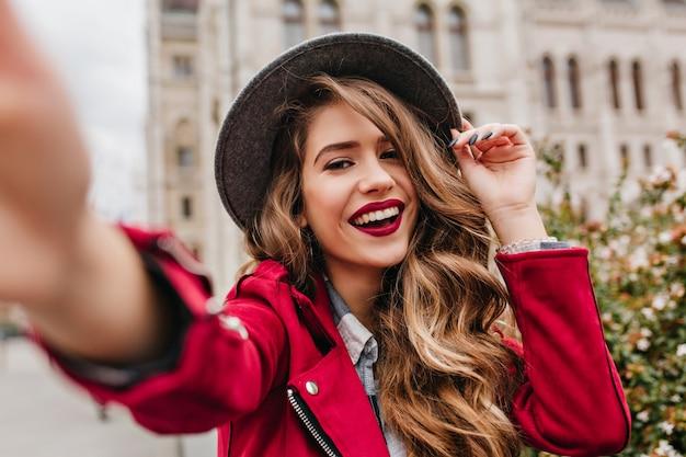 Portret van prachtig wit vrouwelijk model met lichte make-up die energie in goede dag in europa uitdrukken
