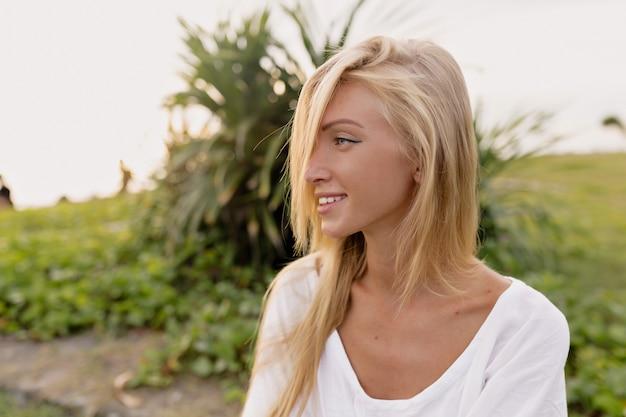 Portret van prachtige 20s europese vrouw met lang haar in witte zomerjurk lachen en wegkijken tijdens het wandelen op het zand bij de zee