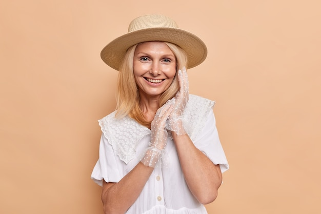 Portret van prachtige aristocratische vrouw met een aangename uitstraling glimlacht gelukkig houdt handen bij elkaar draagt fedora witte jurk en kanten handschoenen drukt positieve emoties uit poses tegen beige muur