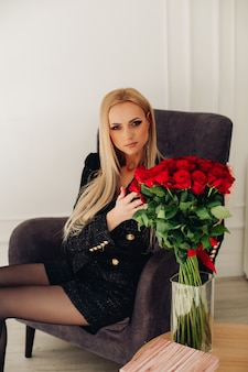 Portret van prachtige blonde blanke vrouw in zwarte korte broek en jas aanraken van rode rozen in vaas zittend in donkergrijze fauteuil.