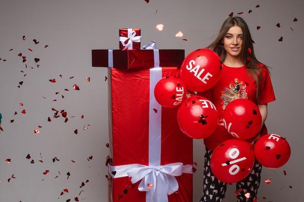 Portret van prachtige brunette in pyjama's met verschillende rode ballonnen