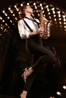 Portret van prachtige brunette model vrouw in modieus formeel pak met saxofoon spelen op restaurant