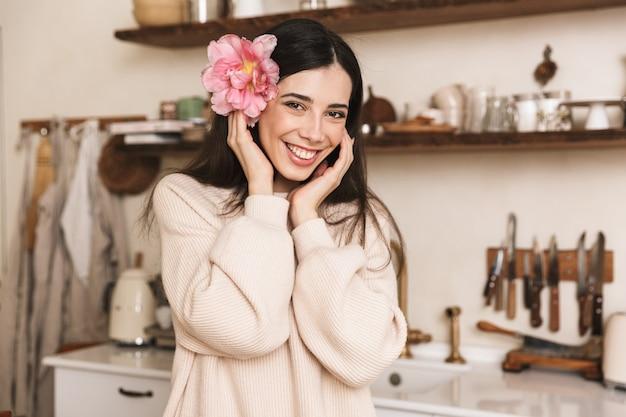 Portret van prachtige brunette vrouw glimlachend en kijken naar camera met mooie bloem in haar haar binnen
