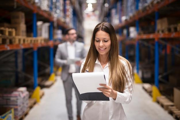 Portret van prachtige brunette vrouw manager bedrijf in magazijn logistiek centrum controleren goed geklede succesvolle vrouw distributie controleren terwijl ceo achter haar loopt.