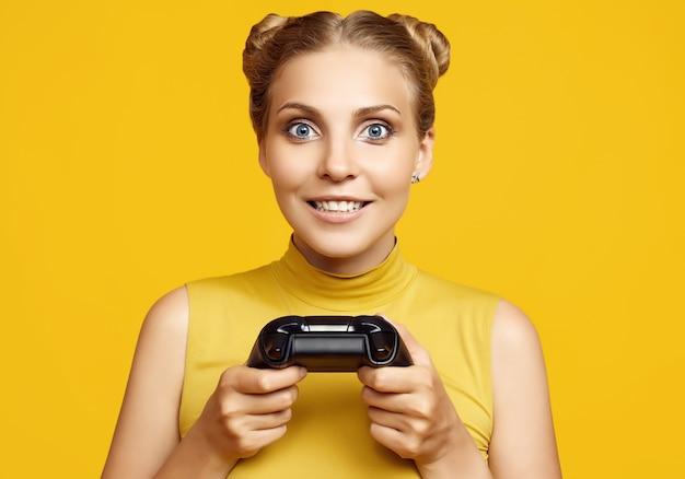 Portret van prachtige gelukkig blonde gamer meisje spelen van videospellen met joystick op gele achtergrond in de studio
