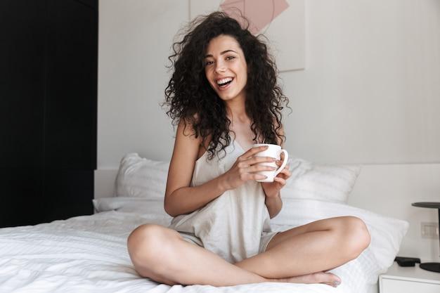 Portret van prachtige gelukkige vrouw met lang krullend haar, zittend op bed met wit schoon linnen thuis in de ochtend, en kopje thee te houden