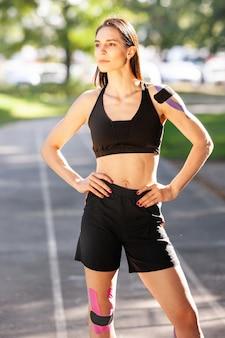 Portret van prachtige gespierde brunette vrouw, gekleed in zwarte sport outfit poseren buitenshuis