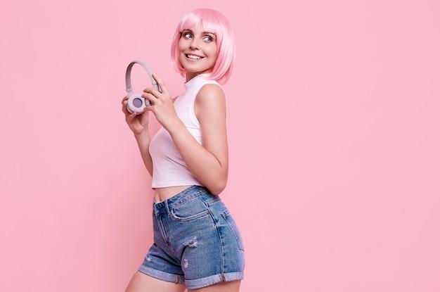 Portret van prachtige heldere hipster meisje met roze haren geniet van de muziek in koptelefoon op kleurrijk