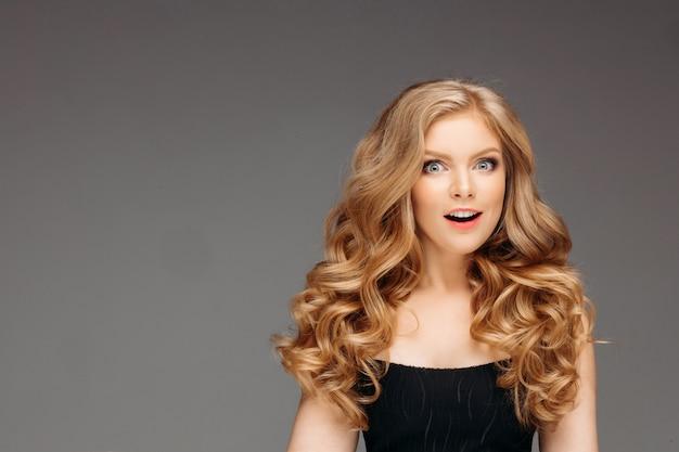 Portret van prachtige jonge blondevrouw met lang haar, het glimlachen