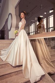 Portret van prachtige jonge bruid met mooie make-up en kapsel in trouwjurk