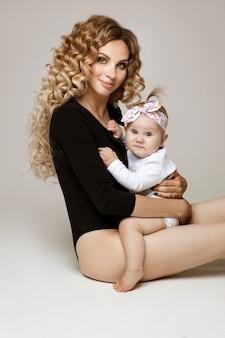 Portret van prachtige jonge volwassen vrouw met golvend haar in zwart lichaam knuffelen schattige baby dochter zittend op de vloer en glimlachen