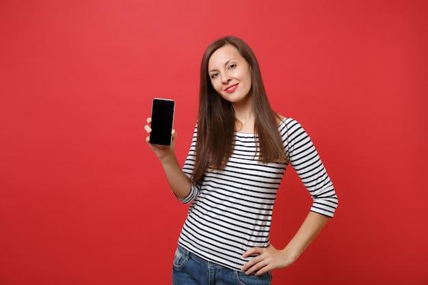 Portret van prachtige jonge vrouw in gestreepte kleding met mobiele telefoon met leeg zwart leeg scherm geïsoleerd op heldere rode achtergrond. mensen oprechte emoties levensstijl concept. bespotten kopie ruimte.