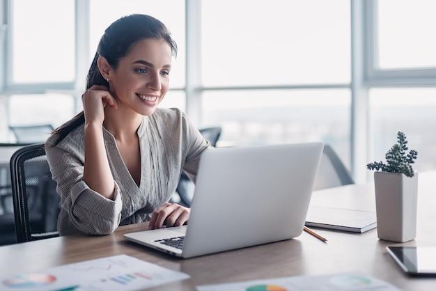 Portret van prachtige lachende jonge vrouw met behulp van laptopcomputer op de werkplek