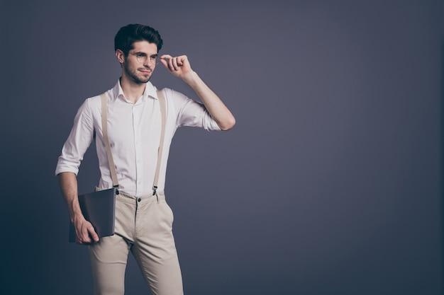Portret van prachtige man ondernemer klaar werk in opstarten houden laptop staren copyspace touch bril dragen stijlvolle outfit.