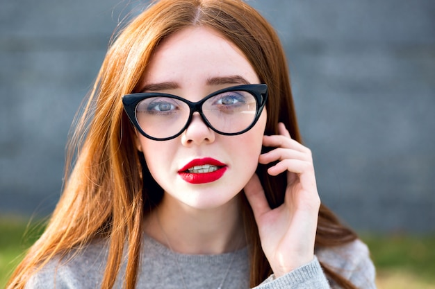 Portret van prachtige schattige mooie gember tiener meisje close-up, duidelijke vintage zonnebril, student stijl