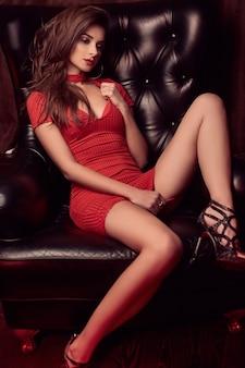 Portret van prachtige schoonheid jonge brunette vrouw in rode jurk zittend in een lederen stoel