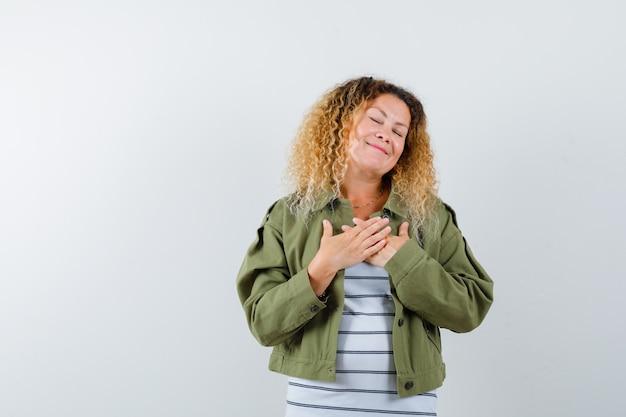 Portret van prachtige vrouw hand in hand op de borst, ogen sluiten in groene jas, shirt en tevreden vooraanzicht kijken
