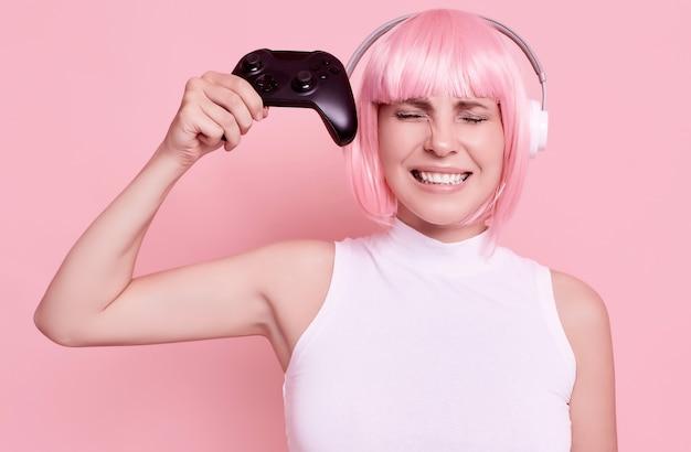 Portret van prachtige vrouw met roze haar spelen van videospellen met joystick in studio