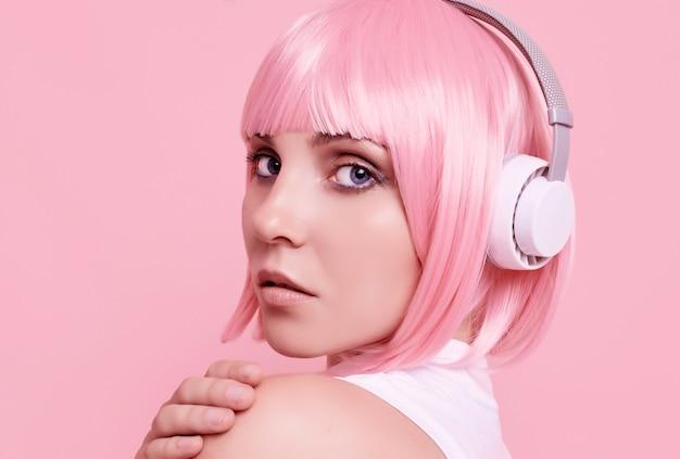 Portret van prachtige vrouw met roze haren geniet van de muziek in de koptelefoon
