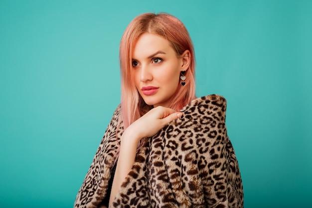 Portret van prachtige vrouw met roze haren in stijlvolle winter pluizige jas met luipaard print