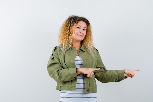 Portret van prachtige vrouw wijzend naar de rechterkant in groene jas, overhemd en op zoek vrolijk vooraanzicht