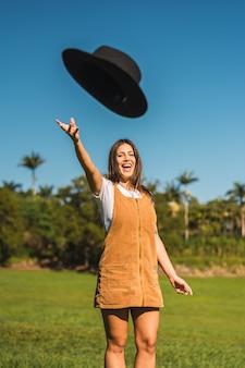 Portret van prachtige witte vrouwelijke model zwarte hoed gooien in de lucht en wandelen door het veld