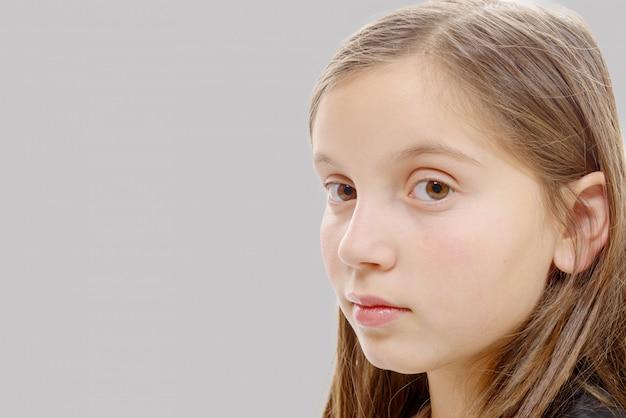 Portret van pre tienermeisje geïsoleerd op grijze achtergrond