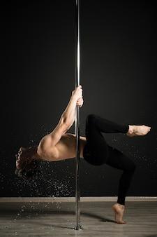Portret van professioneel mannelijk model dat een pooldans uitvoert