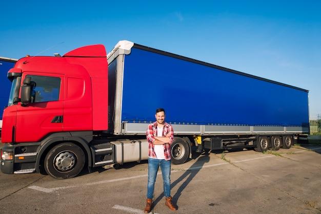 Portret van professionele amerikaanse vrachtwagenchauffeur in vrijetijdskleding en laarzen die zich voor vrachtwagenvoertuig met lange aanhangwagen bevinden