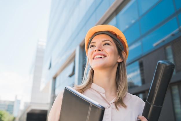 Portret van professionele architectenvrouw die gele helm draagt en zich in openlucht bevindt. ingenieur en architect concept.