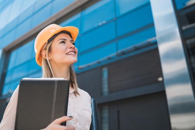 Portret van professionele architectvrouw die gele helm draagt en modern gebouw in openlucht bekijkt. ingenieur en architect concept.