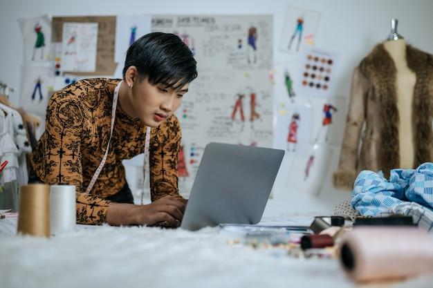 Portret van professionele aziatische jonge mannelijke kleermaker met meetlint op nek die op laptop werkt