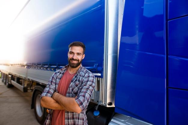 Portret van professionele bebaarde vrachtwagenchauffeur van middelbare leeftijd in vrijetijdskleding met gekruiste armen die zich door zijn vrachtwagen bevinden.
