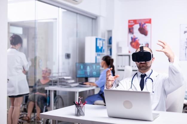 Portret van professionele blanke mannelijke arts in vr-bril die in ziekenhuiskast zit en gebaren maakt met behulp van virtual reality-innovaties terwijl vrouwelijke verpleegster op de achtergrond werkt