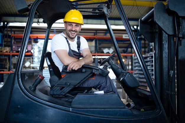 Portret van professionele heftruckchauffeur in het magazijn van de fabriek