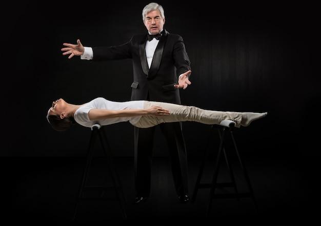 Portret van professionele hypnotiseur op zwarte achtergrond die met jonge vrouw werken