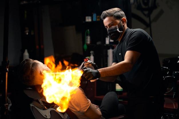 Portret van professionele kapper in zwarte rok, handschoenen en masker op zijn mond haar brandbehandeling geven aan bebaarde mannelijke klant. knappe kapper met behulp van extreme technologie voor ontharing