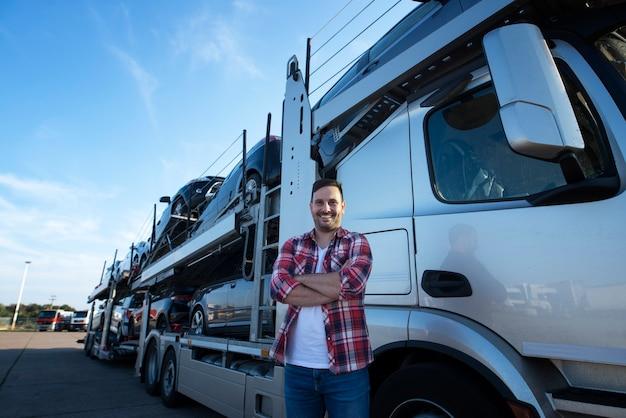 Portret van professionele lachende vrachtwagenchauffeur met gekruiste armen auto's naar de markt vervoeren