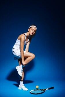 Portret van professionele tennisspeelster met racket en bal opzij