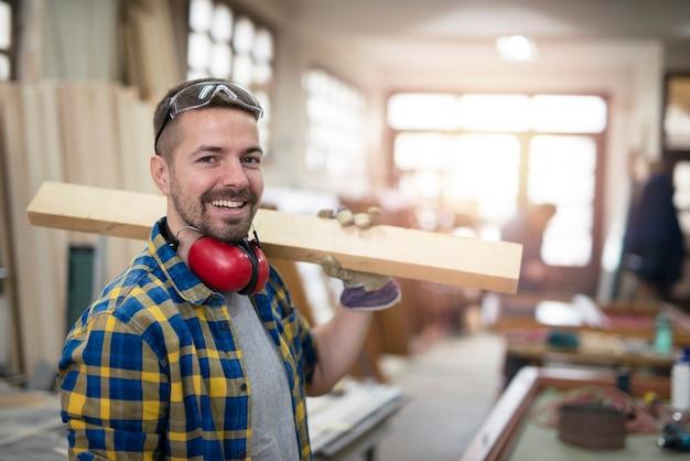 Portret van professionele timmerman die houten plankmateriaal op zijn schouder houdt en glimlacht