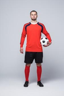 Portret van professionele voetballer in rood overhemd dat op wit wordt geïsoleerd