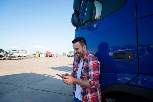 Portret van professionele vrachtwagenchauffeur van middelbare leeftijd die zich door zijn vrachtwagen bij vrachtwagenstop bevindt die tabletcomputer gebruikt