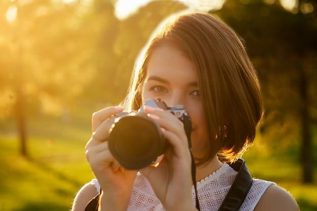 Portret van professionele vrouwelijke fotograaf in het park fotograferen op een camera. fotoshoot fotosessie in de stad.